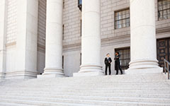 A well dressed man and woman converse on the steps of a legal or municipal building